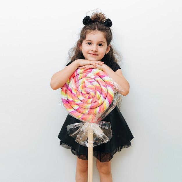 Jolie petite fille avec sucette géante Photo gratuit