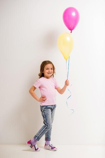 Jolie petite fille tenant des ballons roses et jaunes. Photo Premium
