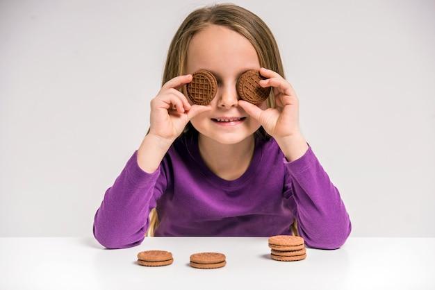 Jolie petite fille tenant un cookie à la table. Photo Premium