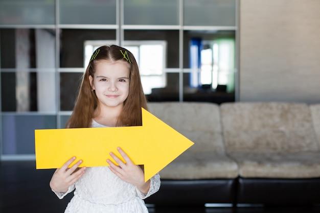 Jolie petite fille tenant une pancarte jaune blanche sous la forme d'une flèche montrant le droit Photo Premium