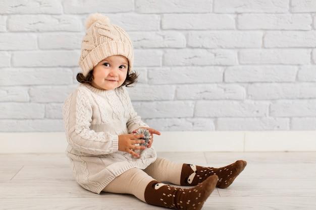 Jolie Petite Fille Tenant Une Pomme De Pin Photo gratuit