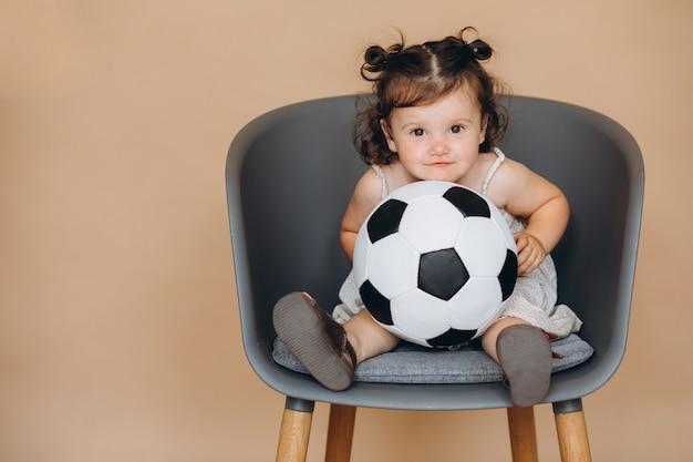 Une jolie petite fille tient le ballon, regarde le football et encourage son équipe Photo Premium