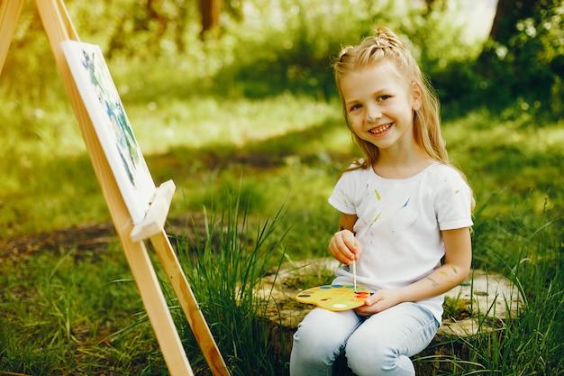 Jolie petite fille en train de peindre dans un parc Photo gratuit