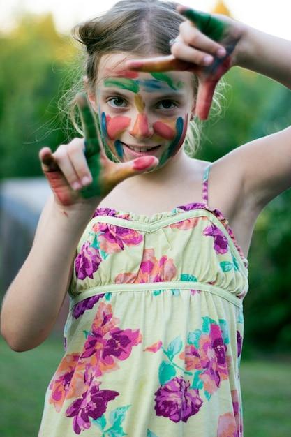 Jolie petite fille avec visage coloré et mains formant un doigt Photo Premium