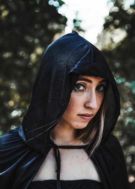 Jolie sorcière en cagoule noire dans un fourré ensoleillé Photo gratuit
