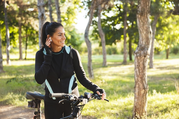 Jolie Sportive Avec Un Vélo Dans Le Parc, écoutant De La Musique Avec Des écouteurs Sans Fil Photo Premium