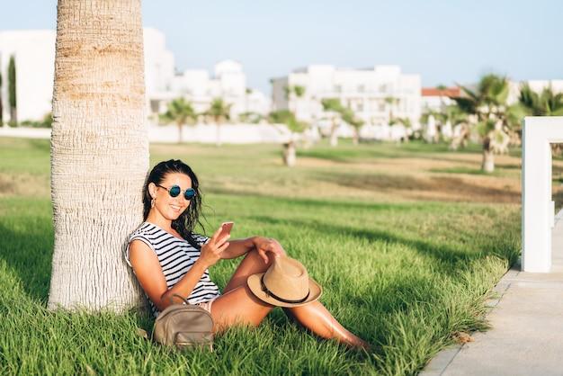 Jolie touriste asiatique fille assise sous le palmier et en utilisant son téléphone intelligent. Photo Premium