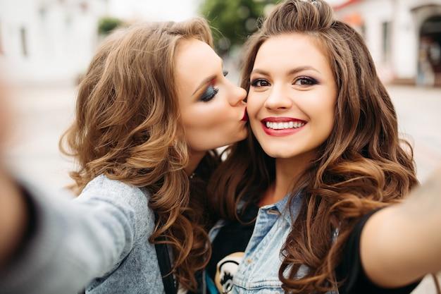 Jolies adolescentes avec des coiffures et des lèvres rouges, souriant à la caméra. Photo Premium