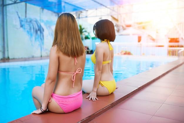 Jolies femmes au bord de la piscine Photo gratuit