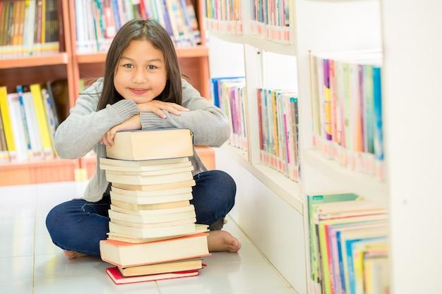 Jolies filles et beaucoup de livres Photo gratuit
