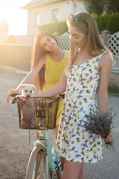 Jolies filles avec un chien à vélo Photo gratuit