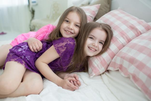 Jolies filles en robes roses et violettes étaient au lit Photo Premium
