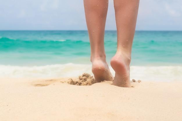 Jolies jambes lisses des femmes sur la plage de sable blanc Photo Premium