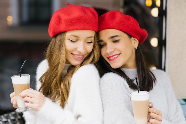 Jolies Jeunes Femmes En Bérets Tenant Des Tasses De Café Dans Leurs Mains Photo Premium