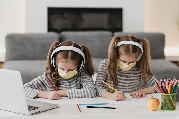 Jolis Jumeaux Portant Des Masques Médicaux à L'intérieur Photo Premium