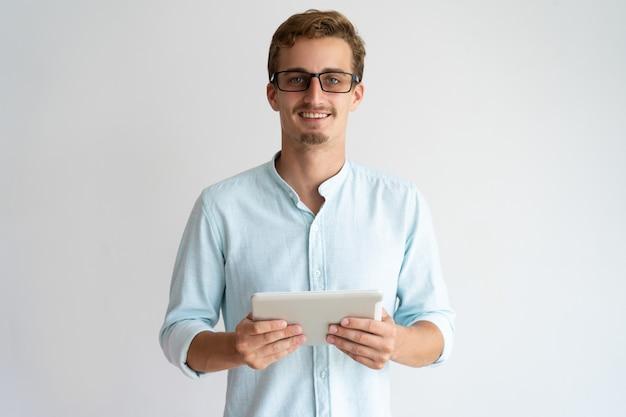 Jolly a excité le beau spécialiste masculin travaillant avec la tablette et regardant la caméra. Photo gratuit