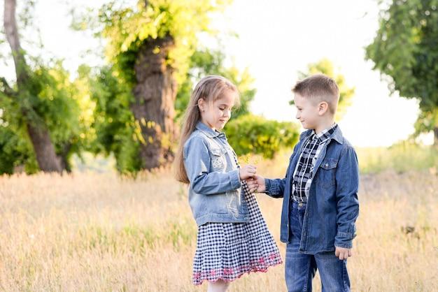Jouer des enfants dans un champ vert pendant une chaude journée d'été Photo Premium