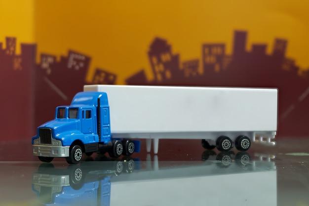 Jouet De Camion Porte-conteneur Bleu Avec Vue De Côté De Remorque Porte-conteneur Simulée, Mise Au Point Sélective, Sur La Ville Flou Photo Premium