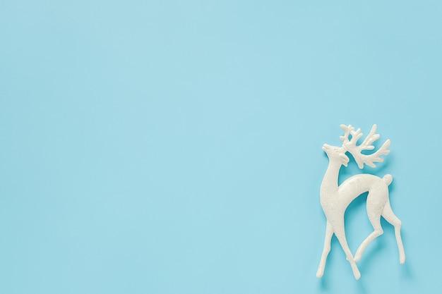 Jouet de cerf blanc décoration de noël sur fond bleu avec espace de copie Photo Premium