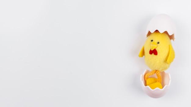 Jouet petit poulet en coquille d'oeuf sur la table Photo gratuit