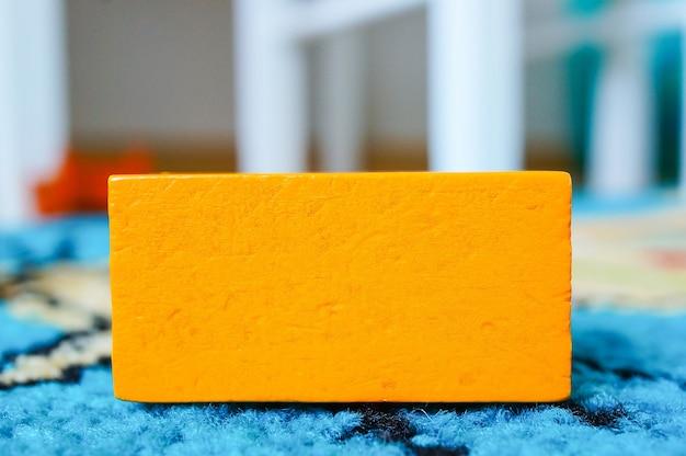 Jouet Rectangulaire Orange Pour Enfants Posé Sur Une Surface Multicolore Photo gratuit