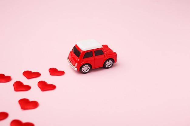 Jouet Rétro Rouge Voiture Rouge Avec Noeud Rouge Pour La Saint Valentin Sur Rose Avec Des Confettis Coeur Photo Premium