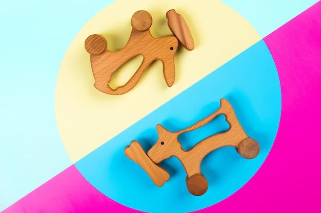 Jouets en bois lapin avec carotte, chien avec un os sur fond isolé rose, bleu et jaune. Photo Premium
