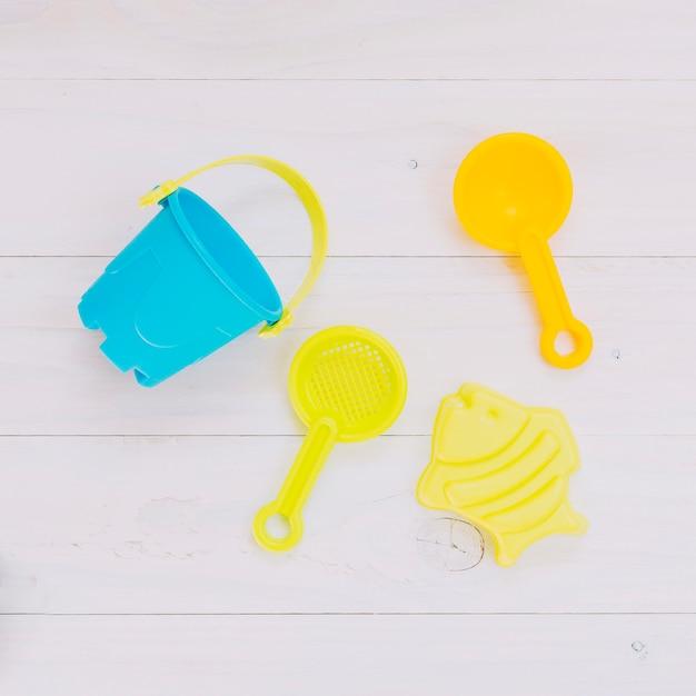 Jouets colorés pour bac à sable sur fond clair Photo gratuit