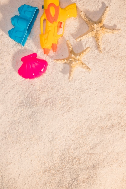 Jouets de plage et étoile de mer sur le sable Photo gratuit