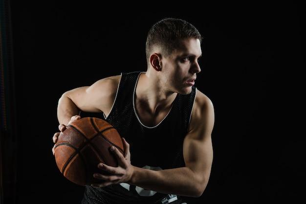 Joueur de basket attraper la balle avec les deux mains Photo gratuit