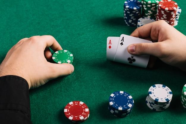 Joueur avec deux as et des jetons jouant au poker Photo gratuit