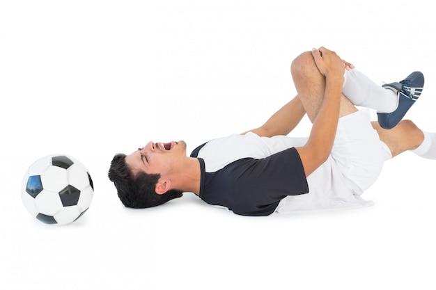 Joueur de foot couché et criant de douleur Photo Premium