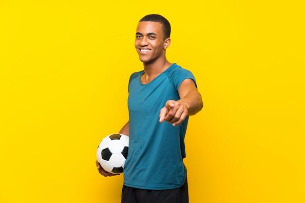 Un joueur de football afro-américain vous montre du doigt avec une expression confiante Photo Premium