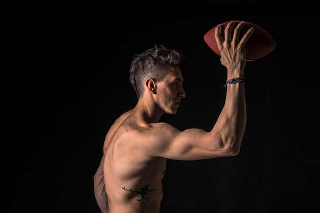 Joueur de football américain avec abs sur fond noir Photo Premium