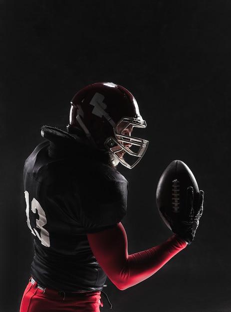 Joueur De Football Américain Posant Avec Ballon Sur Mur Noir Photo gratuit