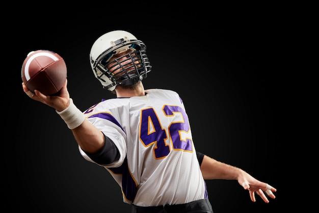 Joueur de football américain sportif sur fond noir. sport . Photo Premium