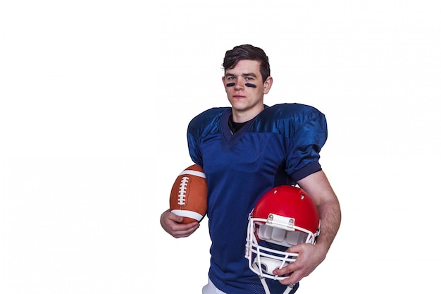 Joueur de football américain tenant une balle et un casque Photo Premium