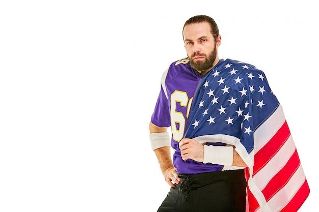 Joueur De Football Américain Avec Uniforme Et Drapeau Américain Fier De Son Pays, Sur Un Espace Blanc. Photo Premium