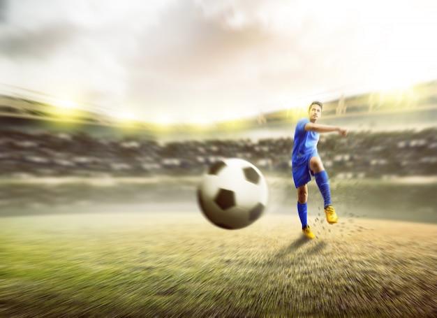 Joueur de football asiatique homme botter le ballon Photo Premium
