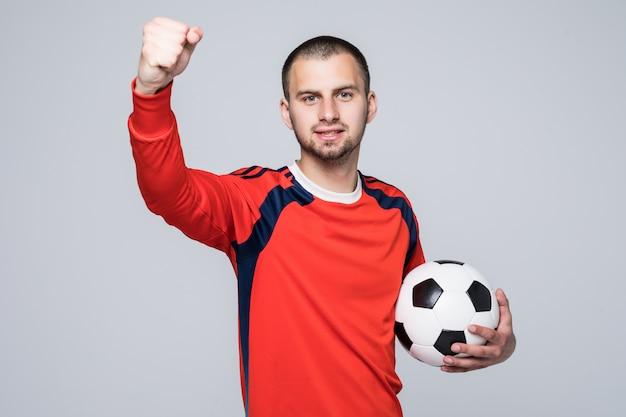 Joueur De Football Excité En T-shirt Rouge Tenant Un Concept De Victoire De Football Isolé Sur Blanc Photo gratuit