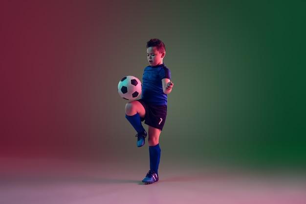 Joueur De Football Ou De Football Masculin Adolescent, Garçon Sur Fond Dégradé En Néon - Mouvement, Action, Concept D'activité Photo gratuit