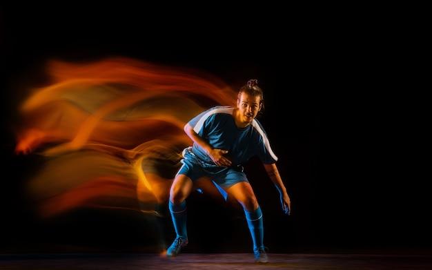 Joueur De Football Ou De Football Sur Studio Noir Photo gratuit