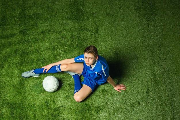 Joueur De Football Garçon Assis Sur L'herbe Verte Photo gratuit