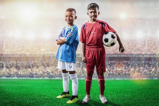 Joueur de football rival en jersey bleu et rouge, debout et pose devant la caméra dans le stade Photo Premium