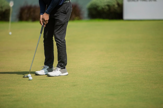 Joueur de golf au putting green frappant la balle dans un trou Photo Premium