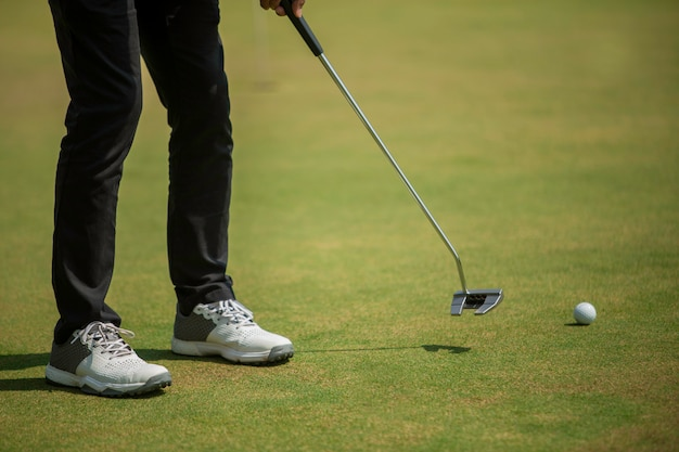 Joueur de golf au putting green frappant la balle dans un trou Photo Premium