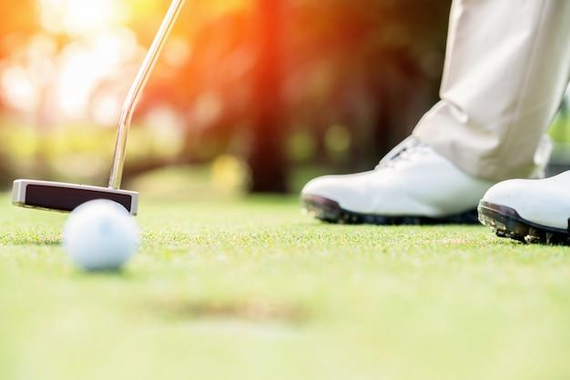 Joueur de golf sur le green frappant la balle dans un trou Photo Premium
