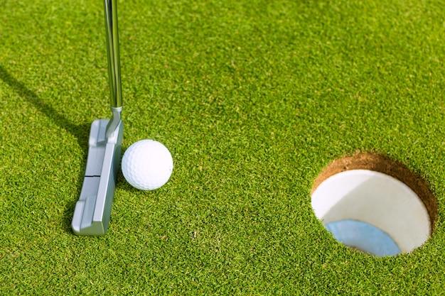 Joueur de golf mettre la balle dans le trou Photo Premium