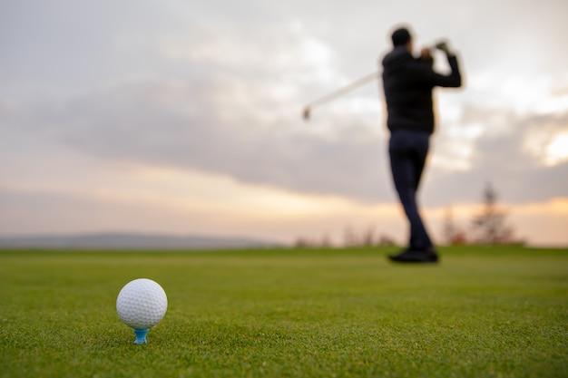 Un joueur de golf prépare la balle pour être tiré sur le terrain de golf Photo Premium