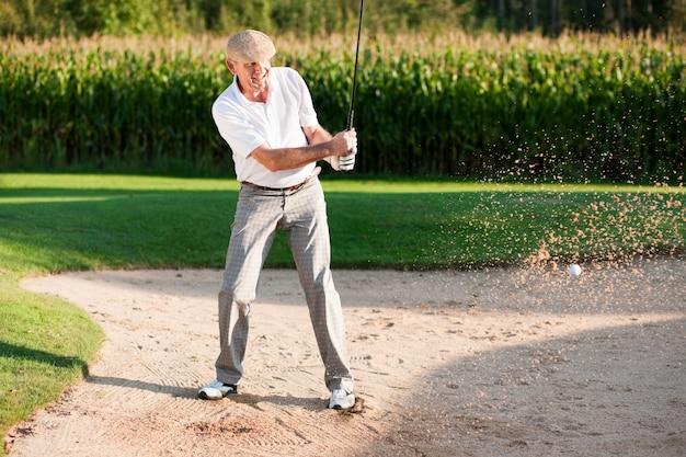 Joueur de golf senior dans un bac à sable Photo Premium